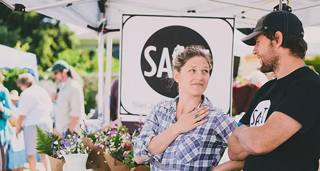 San Juan Island Salt photo of woman and man talking at a Farmer's Market with the Salt logo banner in the background flanked by packaged flowers