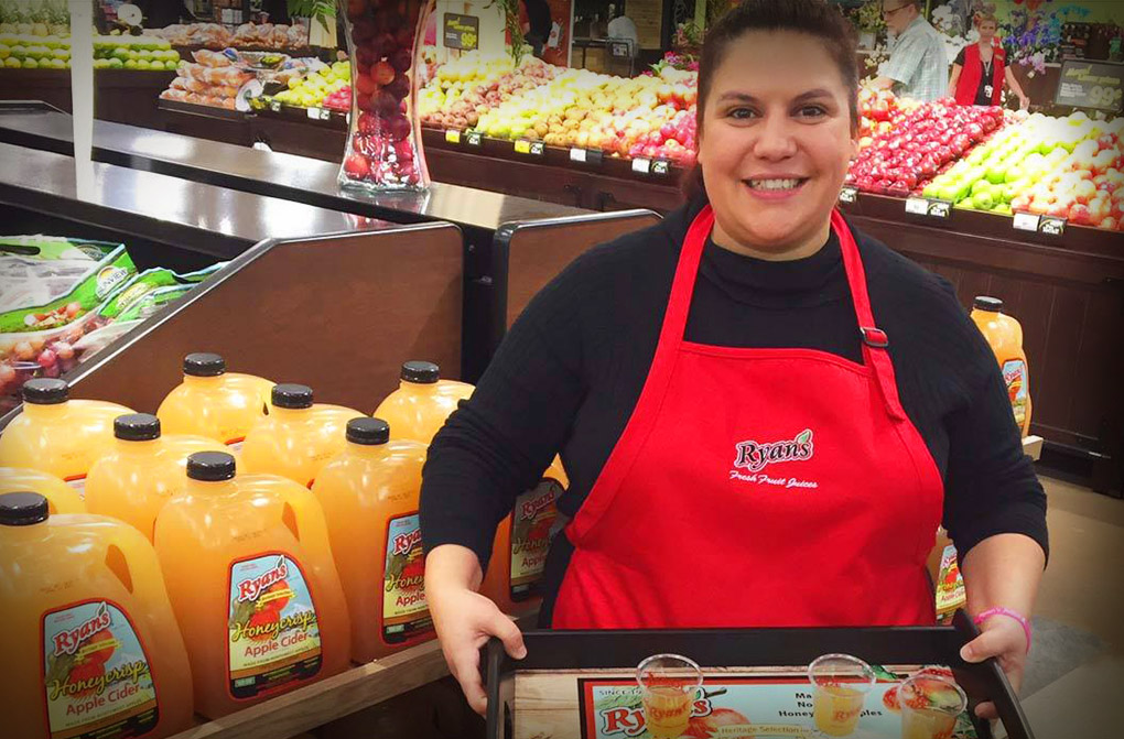 Woman standing in a grocery store produce department holding a tray of apple cider smiling
